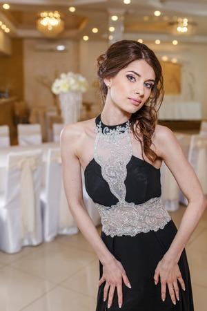 fresh graduate: Portrait of young beautiful brunette woman wearing black prom dress.