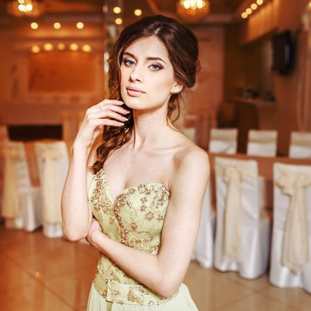 Teenage girl wearing fancy prom dress, posing on  school-leaving party.