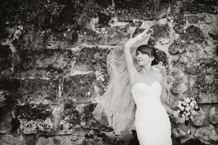 marriageable: Beautiful bride playing with veil against rock wall