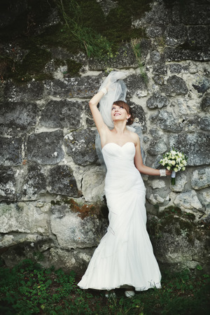 marriageable: Bride playing with veil against rock wall. Stock Photo