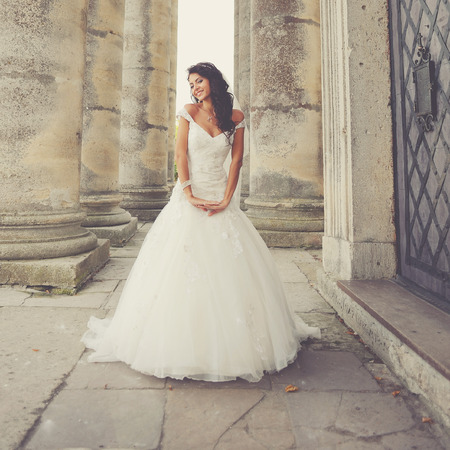 woman dress: Beautiful bride posing on the steps of an old church