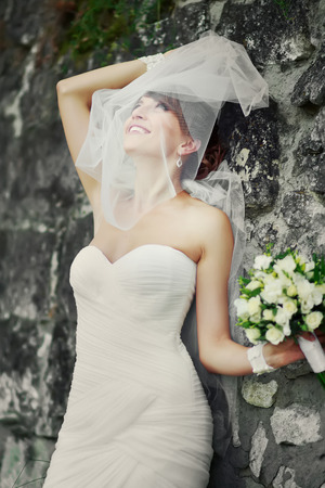 nuptial: Beautiful bride playing with veil.  Summertime picture.
