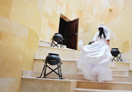 upstairs: Beautiful young bride walks upstairs. Stock Photo