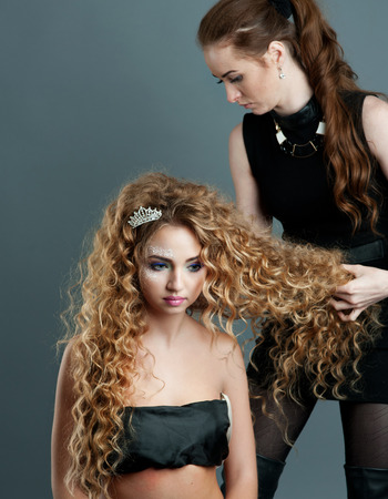 coiffeur: Young hairdresser giving  new hair style to female teen customer.