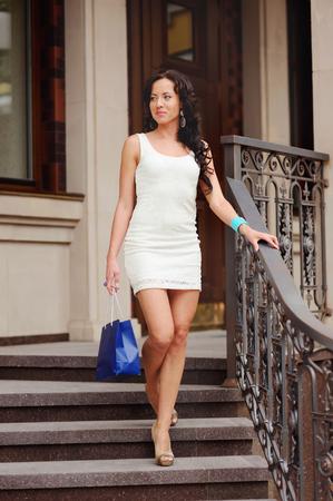 bajando escaleras: Mujer joven morena en vestido blanco con bolsa de compras caminando por las escaleras. Foto de archivo