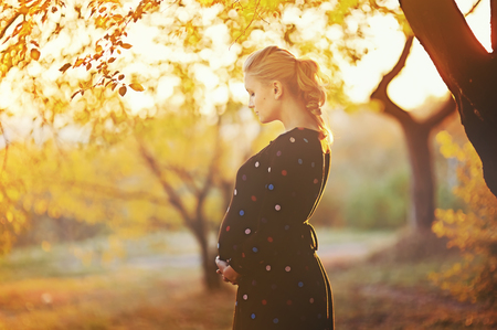 woman only: beautiful pregnant young woman outside, warm sunny picture