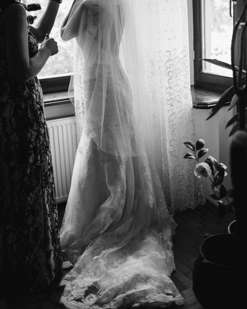 fiance: Happy bridal morning. Fiance getting ready, applying make up.  Wedding picture in black and white. Stock Photo