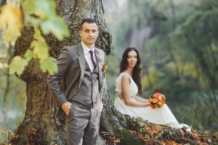 newlywed couple: Wedding couple in forest next to big old tree.  Groom and bride together.