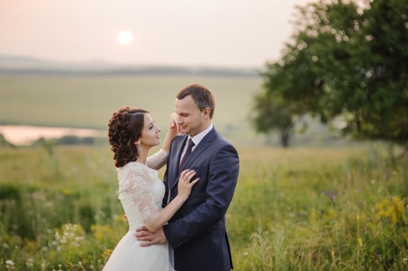 fiance: Wedding couple at countryside during sunset. Groom and bride together.