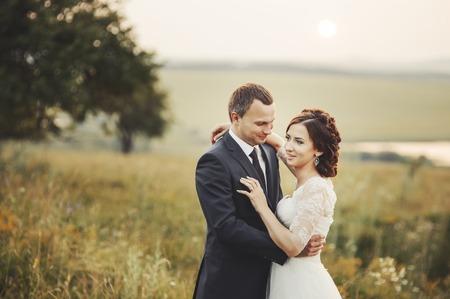 matrimonio feliz: El novio y la novia en el campo. Pares de la boda juntos posando durante la puesta de sol en el campo de verano.