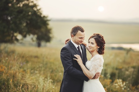mariage: Groom and bride at countryside. Wedding  couple together posing during sunset at summer field.