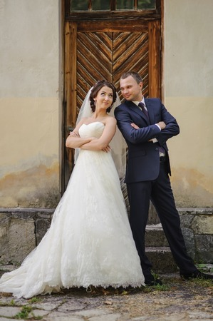 fiance: Wedding summer couple together posing against old fashioned door.