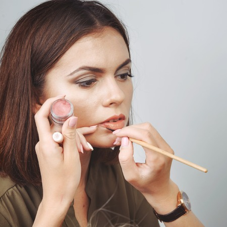 make up applying: Young woman having make up applying by artist. Stock Photo