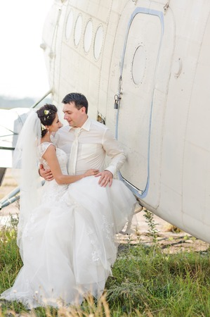 fiance: Bride and groom next to old aircraft. Wedding summer couple together posing against brick wall.