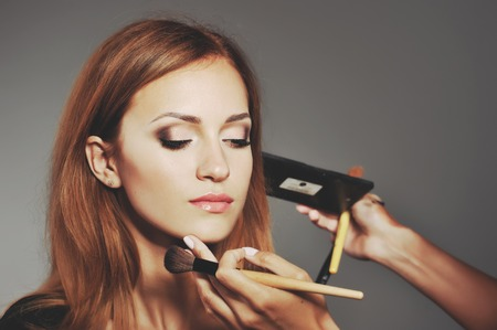 Young woman having make up applying by artist in studio.