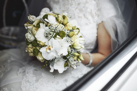Bride with wedding bouquet sitting in a car.