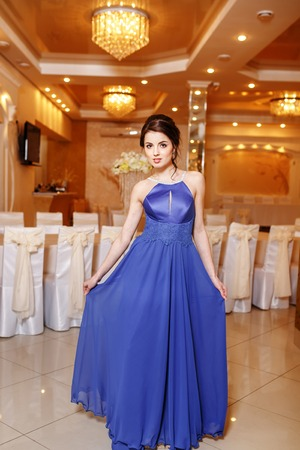 fresh graduate: Interior portrait of young brunette woman wearing blue prom dress.