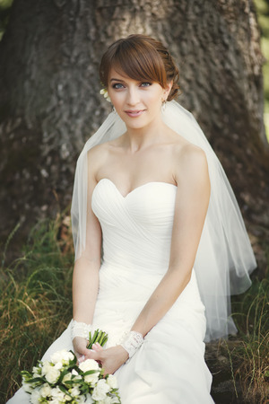 marriageable: Beautiful bride posing in garden. Summertime picture. Stock Photo