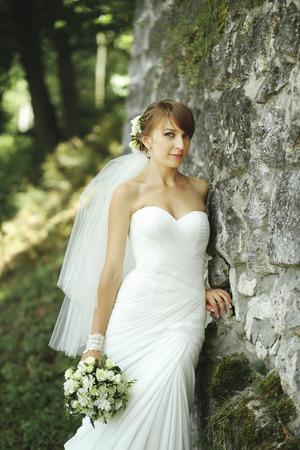 marriageable: Happy bride posing in garden. Summertime picture.