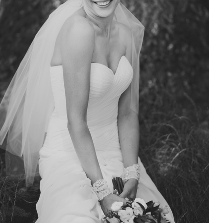 wedding dress: Black and white picture of a bride with bouquet outside. Stock Photo
