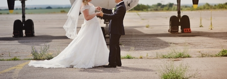 Happy bridal couple against old aircraft.  Wedding summer picture.