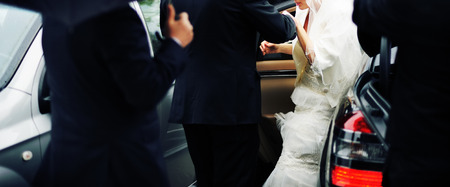 going out: Wedding picture of  bride going out from the car. Stock Photo