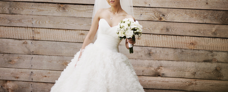 Wedding picture of happy bride against wooden background.
