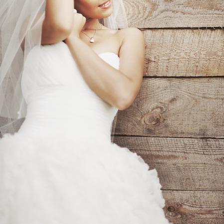 Trouwfoto van de gelukkige bruid tegen houten achtergrond.
