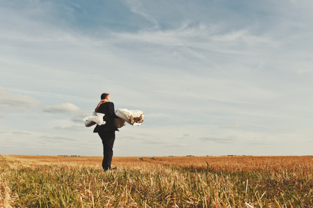 wed: Young newly wed couple at field. Groom and bride together. Stock Photo