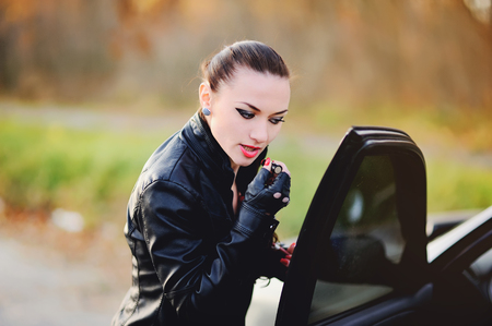 leather gloves: Young woman in black leather jacket with lipstick, looking into window of a car