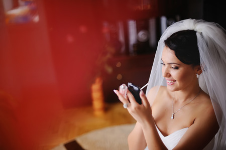 marriageable: Young bride is getting ready at home, having make up, using phone like a  mirror.