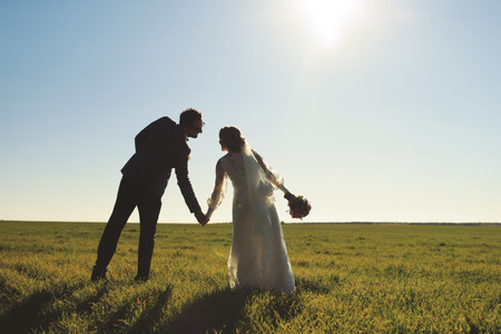 Young newly wed couple at field. Groom and bride together. Stock Photo