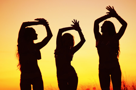 silhouettes of young women against sunset sky