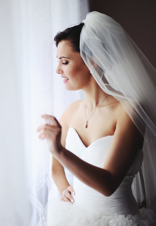 marriageable: Adorable fiancee whaiting for the groom. Young brunette bride in the morning at home.