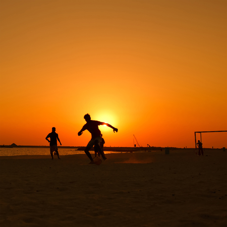 amateur: Amateur playing football  at beach  during sunset. Foto de archivo