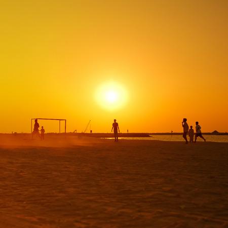 amateur: Jugando al f�tbol amateur en la playa durante la puesta de sol.