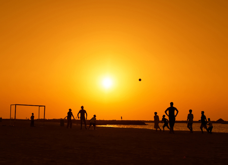 sports field: Amateurs playing football at Jumeira beach in Dubai during sunset.