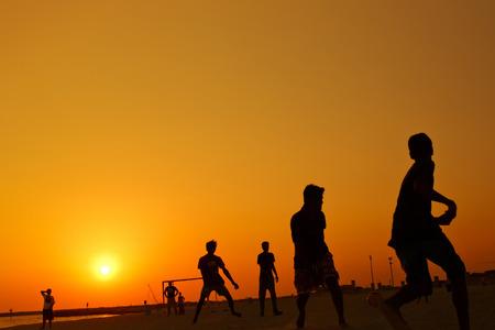 amateur: Jugando al fútbol amateur en la playa durante la puesta de sol.