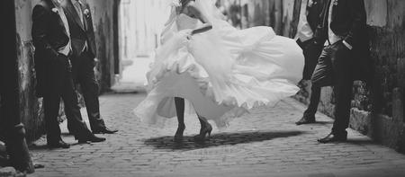 Gelukkige bruid dansen rond jongens. Trouwdag Stockfoto