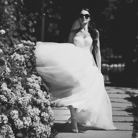 nuptial: Beautiful bride in sunglasses walking in garden. Picture in black and white. Stock Photo