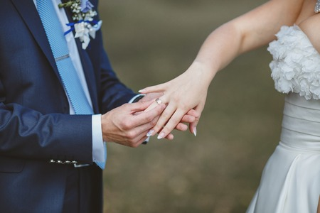 nuptial: Groom puts wedding ring on brides finger. Wedding couple put trust in the future.