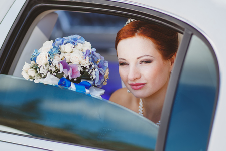 beautiful red bride with bouquet sitting in limo