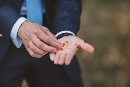 nuptial: Hands of groom with golden wedding rings. Newlyweds in love. Stock Photo