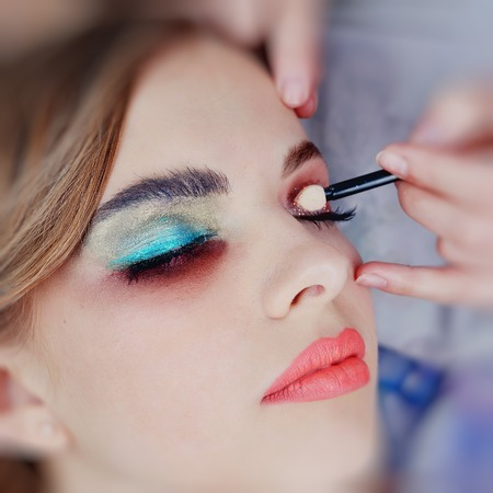 Eye makeup artist applying eyeshadow, close up of smokey style