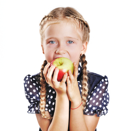 plaits: School kid with plaits bites apple. Cute little girl at white background. Stock Photo