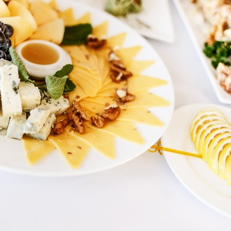 Plate with different cheese at banquet table in restaurant served with different meals. Ready for wedding reception.