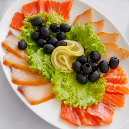 food drink industry: Salmon olives and lemon on plate. Banquet Table in restaurant served with different meals. Ready for wedding reception. Stock Photo