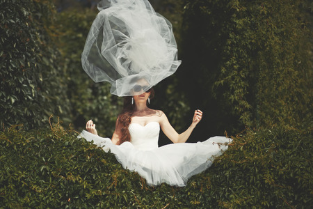 Stylish bride with flying veil. Young happy  fiancee in park.
