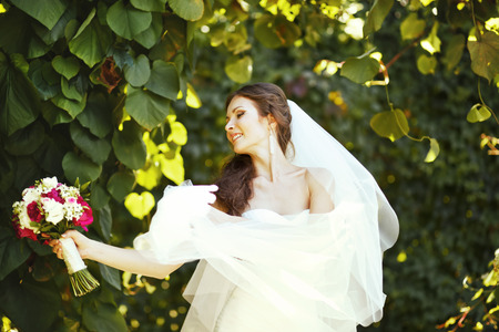 fiancee: Young caucasian bride posing with bouquet in garden. Stock Photo