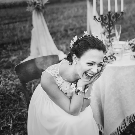 chear: Bride burst of laughing, sitting near wedding decorations on table. Stock Photo